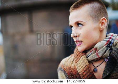 Portrait of young beautiful woman with stylish short haircut in the background of a city street close-up.