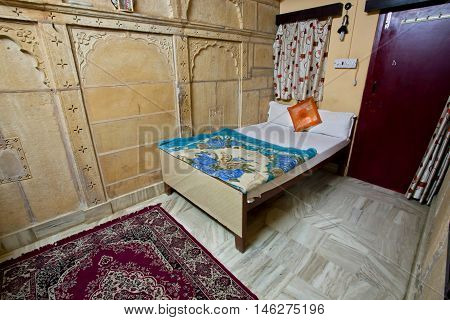 JAISALMER, INDIA - MAR 1, 2015: Interior of a cheep single room with a bed and carpet in a guest house on March 1, 2015. Jaisalmer lies in the heart of the Thar Desert and has a population of about 78000.