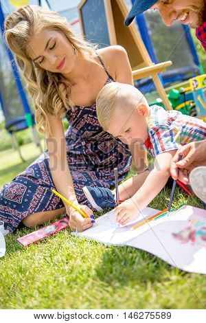 Dad, mom and toddler draws pencils. Happy family draws on the grass in the garden. Kids with parents draws summer, fall on the grass. Happy kid is drawing pencils.