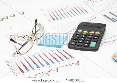 Business still-life of a graph, eyeglasses, sticker, calculator