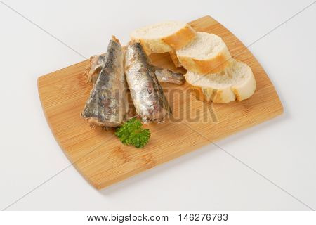 sardines with slices of bread on wooden cutting board
