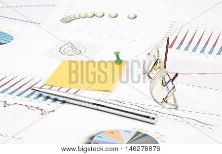 Business still-life of a pen, sticker, graphs, eyeglasses, pushpin