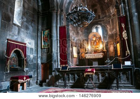 GOGHT ARMENIA - MARCH 23 2016: Inside a Geghard medieval monastery of Kotayk province. Altar ad religious decoration with dim light
