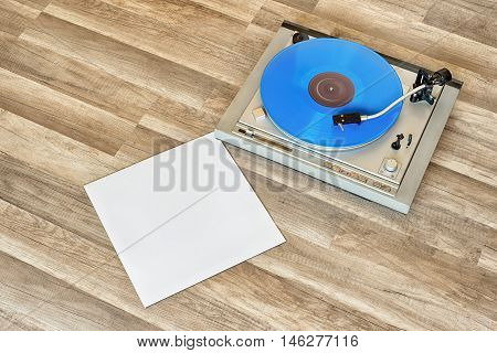 blue vinyl record spinning on the turntable, grunge wooden floor