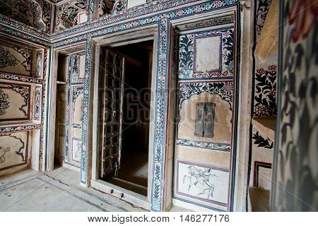 JAISALMER, INDIA - MAR 1, 2015: Painted walls with shelvs in historical mansion Patwon Ki Haveli on March 1, 2015. Jaisalmer lies in the heart of the Thar Desert and has a population of about 78000.