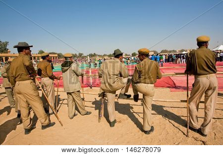 JAISALMER, INDIA - MAR 1, 2015: Group of police men keep order on the popular indian events of Desert Festival on March 1, 2015 in Rajasthan. Every winter Jaisalmer takes the Desert Festival