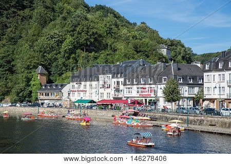 BOUILLON BELGIUM - AUG 13 2016: Belgian medieval city along river Semois in Ardennes with tourists relaxing in boats on August 13 2016 in Bouillon Belgium