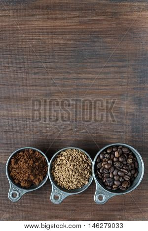 Coffee beans instant coffee and ground coffee in a metal measuring cup on dark wooden background with copy-space top view