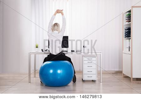 Rear View Of Businesswoman Sitting On Fitness Ball Stretching Her Arms In Office