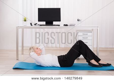 Young Businesswoman Doing Workout On Exercise Mat In Office