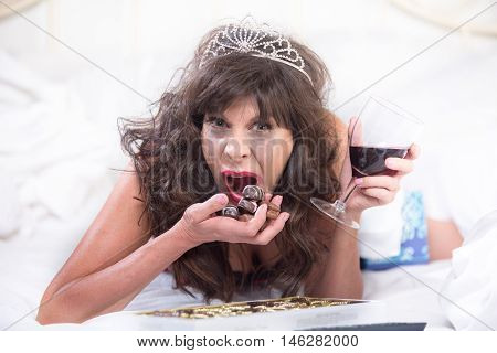 Upset Woman In Tiara Drinking Wine And Cramming Chocolates In Bedroom