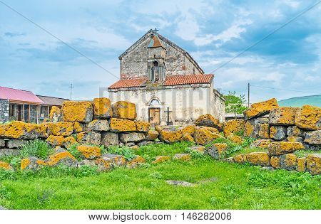 The church of the small village monastery with ruins of the megalithic fortress covered with yellow lichen Saro Georgia.