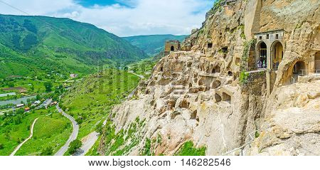 The yellow rocks of archaeological site of Vardzia neighbors with the green valley of Kura river Samtskhe-Javakheti Region Georgia.
