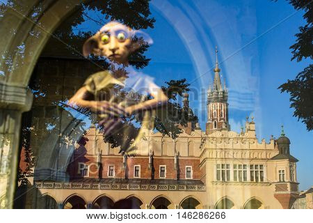 KRAKOW, POLAND - FEB 8, 2016: The reflection of Cloth hall and St Mary's Cathedral in the window of Polonia Wax Museum at Main Market Square. Wax Museum is among the top 10 museums in the city.