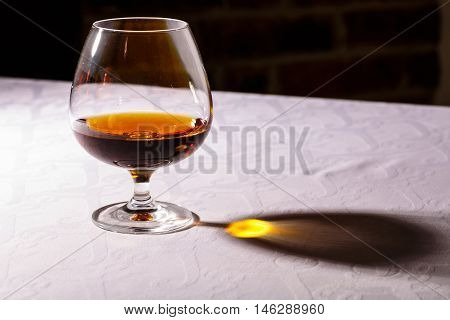 The glare from the glass of French brandy reflected on white tablecloths.