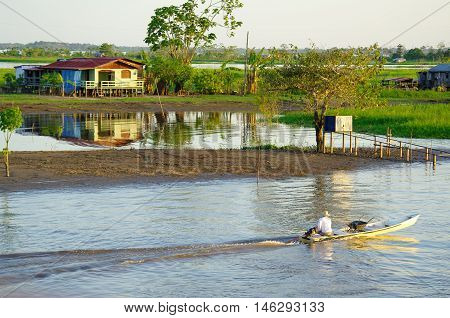 Fisherman On A Rowboat On Amazon River.