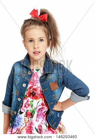 Nice little girl in a dress , denim jacket and red bow on her head . The girl looks straight into the camera . close-up - Isolated on white background