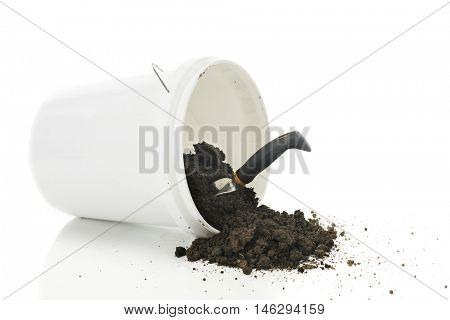 A white plastic, dirt-filled bucket tipped over with dirt falling out.   A hand spade stuck in the dirt.  On a white background.