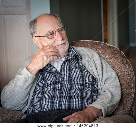 portrait of a grandfather wearing a gray sweater sit on a chair at home