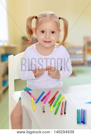 Pretty little blonde girl drawing with markers at the table.Girl holding in hands blue marker.The concept of pre-school education of the child among their peers . on the background of the playroom with shelves for toys. Montessori.