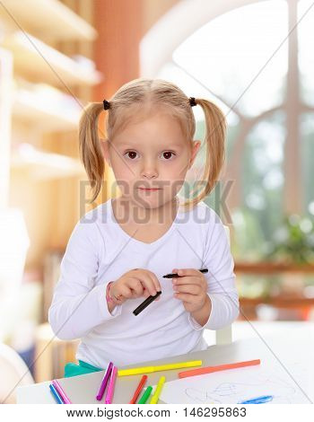 Pretty little blonde girl drawing with markers at the table.Girl holding in hands blue marker.The concept of pre-school education of the child among their peers