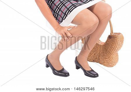 working woman holding her hurting ankle on white background