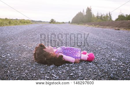 Concept Abandoned PersonAbandoned doll laying on roadvintage tone