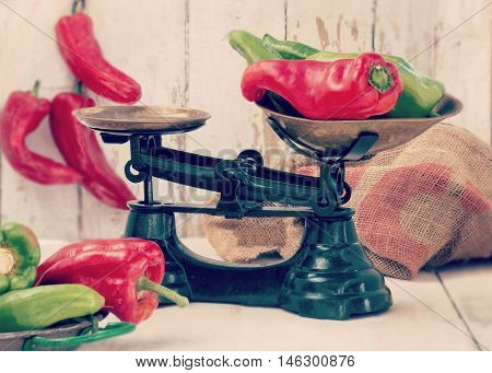 authentic country farmhouse scene showing freshly picked organic green and red peppers  in green scales on an old wooden table. Instagram style filter added , soft window light. bottom blur for copy space