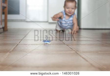 Happy baby boy crawling to grab the pacifier. Hygiene at home concept
