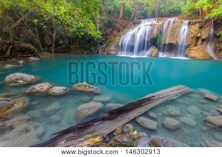 Jangle landscape with flowing turquoise water of Erawan cascade waterfall at deep tropical rain forest. National Park Kanchanaburi Thailand