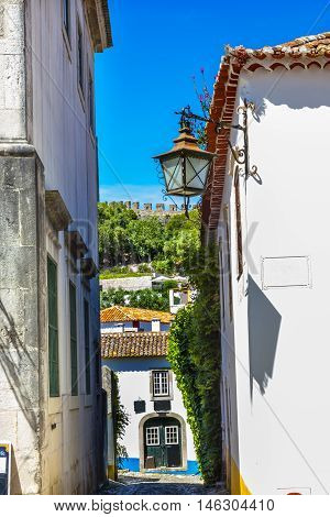 Narrow White Street 11th Century Castle Wall Medieval Town Lamp Obidos Portugal. Castle and walls built in 11th century after town taken from the Moors.