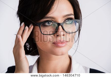 Close-up of young woman's blue eyes behind glasses.