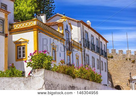 White Yellow Building Street 11th Century Castle Wall Medieval Town Lamp Obidos Portugal. Castle and walls built in 11th century after town taken from the Moors.