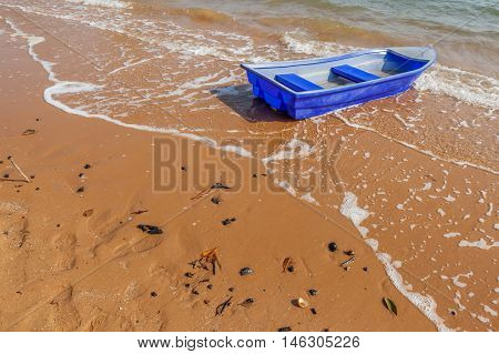 Blue rowboat on the beach with lapped small wave.