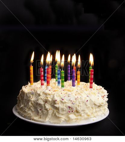 cake on a black background with candles alight