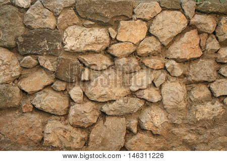 old stone wall background. wall built of auburn stones