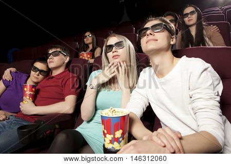 Young people sitting at the cinema, watching a film and eating popcorn. Cinema photo series