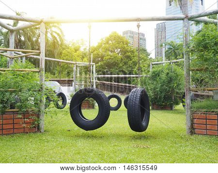 Swings seat made of reused wheel in the city park.