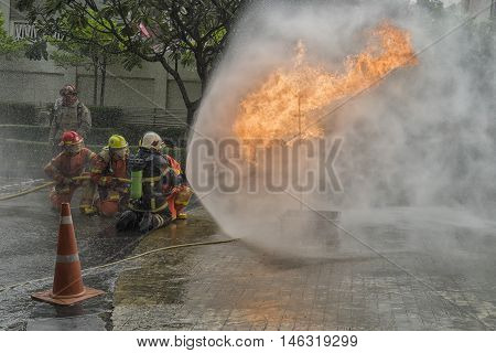 fire drill in day in thailand fireman fight the fire with water - can use to action photo blur background