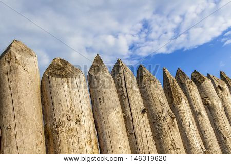 Protective fence of sharp wooden stakes closeup.
