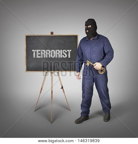 Terrorist text on blackboard with thief and key