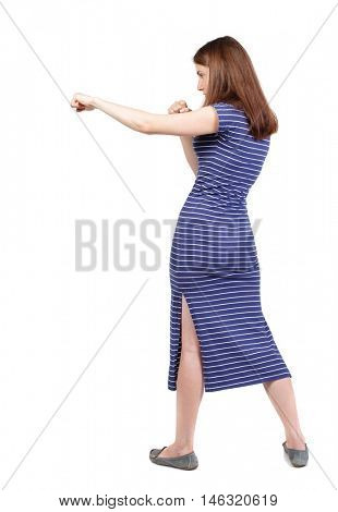 skinny woman funny fights waving his arms and legs. brunette in a blue striped dress stands sideways and hit his foot.