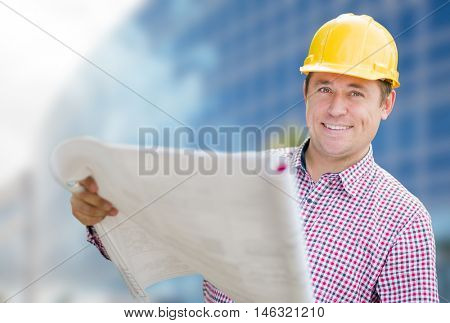 Smiling Contractor in Hardhat Holding Blueprints In Front of Building.