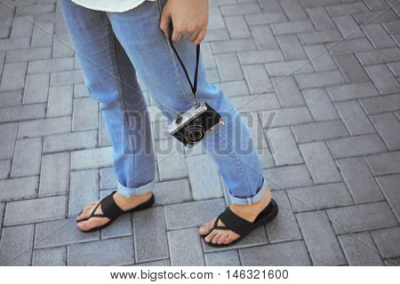 Woman with vintage camera walking on street