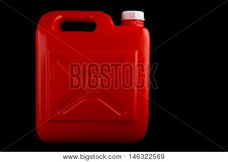 Red plastic fuel container isolated against a black background