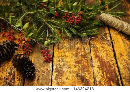 Autumn background. Winter background. Composition with fir branches, fir cones, branches with berries dogwood on a red shabby wooden background. Selective focus