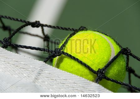 Bright greenish, yellow tennis ball on freshly painted cement court