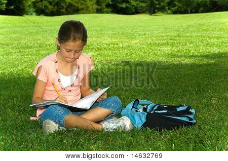 Young girl in park doing school work