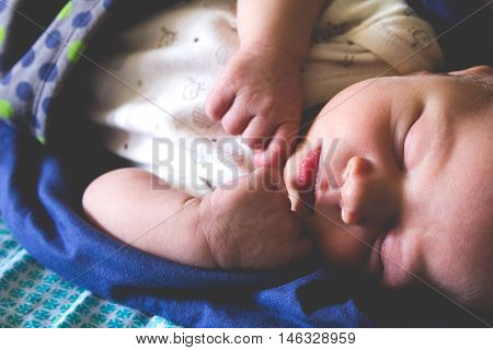 A sweet one month old newborn baby boy is sleeping covered by blanket
