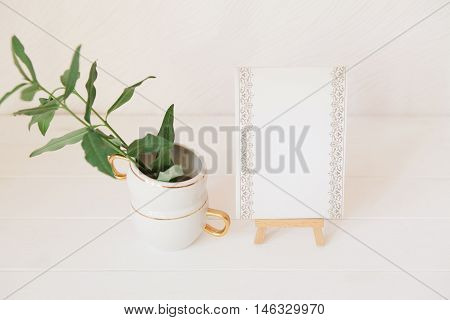 Green Branches With Leaves In Cup And Stylish Paper For Notes On Wooden Easel. Styled Natural Eco Ho